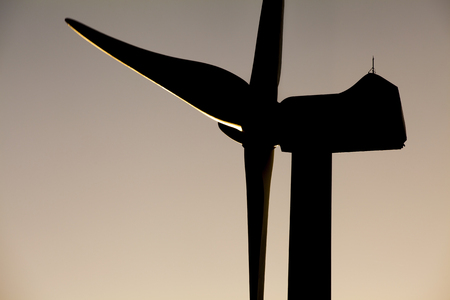 turbina: Sombra del molino de viento. Rayo Volver generador de energía molino de viento en un fondo del cielo del atardecer. Foto de archivo