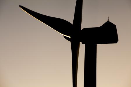 Windmill shadow. Back lightning windmill power generator in a sunset sky background.
