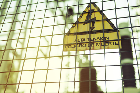 electroshock: Electric transformer station with sign with text High voltage. Danger of death. in Spanish. Stock Photo