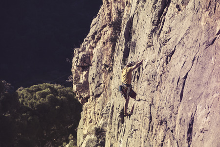 Vintage view of man climbing in a mountain wall.