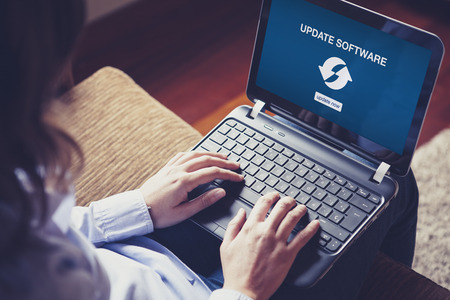 Woman holding a laptop on her knees. Update software notification in the screen. Stock Photo
