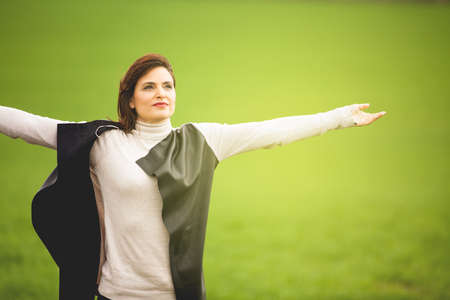 Happy woman breaths deeply with open arms in the middle of nature. Spiritual concept.