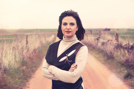 professional woman: Portrait of woman in crossed arms at the countryside. Stock Photo