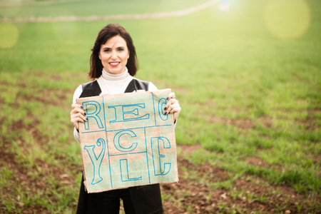 Brunette woman portrait, holding a recycling bag in the countryside. Stock Photo