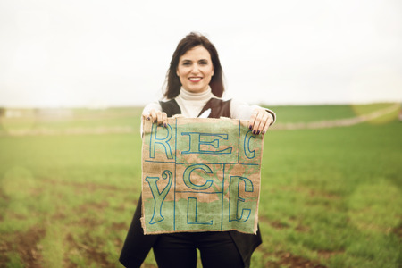 recycle bag: Brunette woman portrait, holding a recycling bag in the countryside. Stock Photo