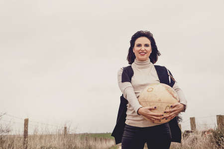 Brunette woman holding a vintage globe in the countryside. Travel concept.