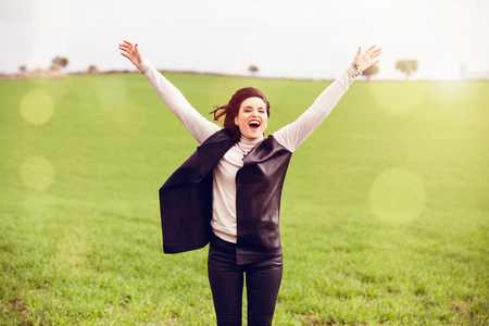 Happy woman jumping in the countryside.