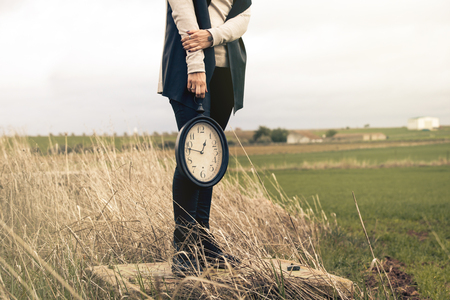expires: Woman hand holding a vintage clock in the middle of the countryside.
