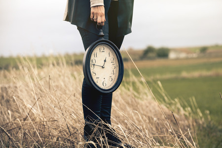 Woman hand holding a vintage clock in the middle of the countryside.
