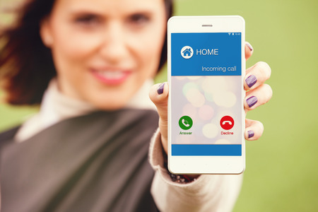 incoming: Incoming call from home in a mobile phone screen. Woman holding smartphone.