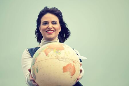 Smiling woman holding a vintage globe in the hands. Traveling concept. Stock Photo