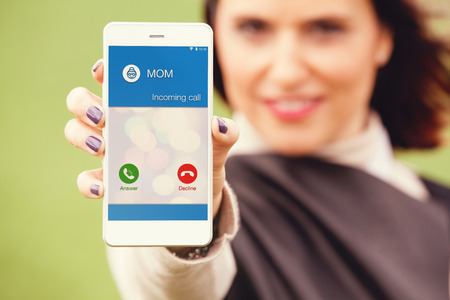 Woman holding a mobile phone with incoming call from Mom.