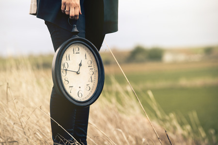 vintage clock: Vintage clock hold by woman outdoors. Time concept. Stock Photo
