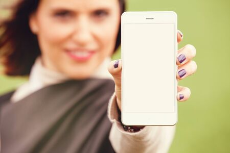 showing: Woman showing an empty mobile phone screen. Stock Photo