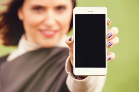 mobile phone screen: Woman showing mobile phone screen.