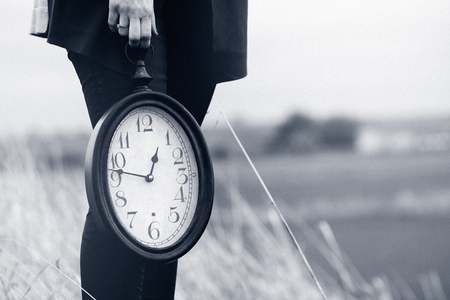 vintage clock: Vintage clock hold by hand. Time concept. Black and white. Stock Photo