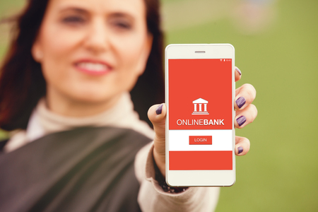 On line bank app in a smart phone screen. Woman holding mobile. Stock Photo