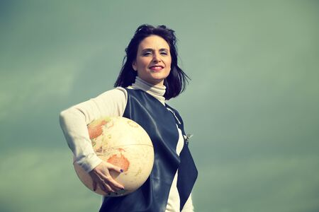 Woman holding a globe with the arm. Traveling concept.