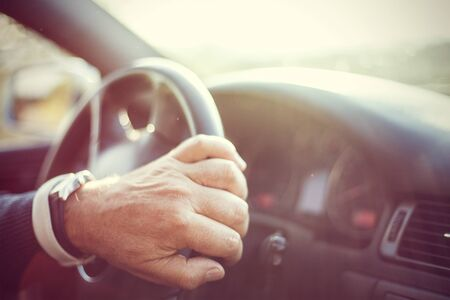 Senior man hand moving the steering wheel inside a car. Stock Photo