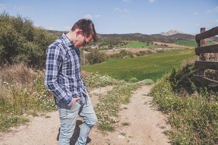 Jeune homme blond posant dans un chemin à la campagne.