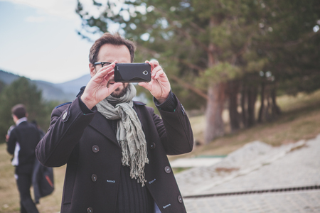 Man taking a photo with a mobile phone outdoors.