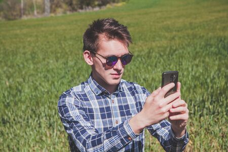 Man taking a photo with a mobile phone at the countryside.