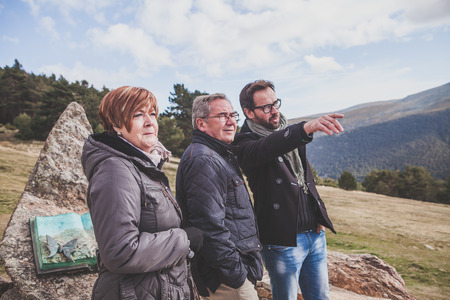 pine three: Senior couple and their adult son visiting the mountain range.
