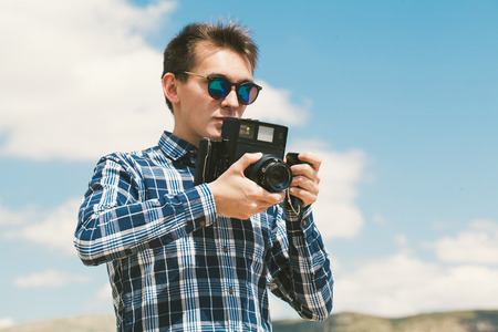 skill: Blond young man holding an old vintage camera. Blue sky background.