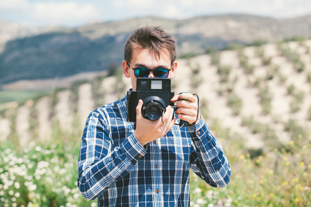 Man taking a photo with an old camera at the countryside.