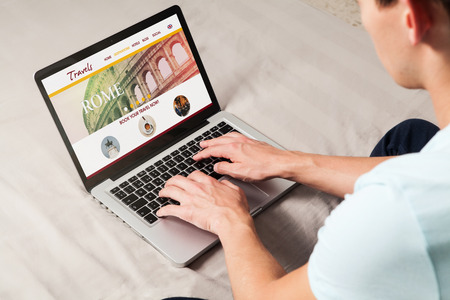 hotel booking: Man sitting at home using a laptop for booking travel destination.