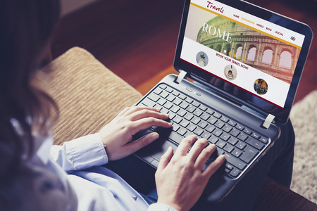 woman searching: Travel website in a laptop screen. Woman searching for destination on line at home. Stock Photo