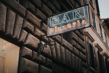 Vintage pizza neon lettering in Rome.