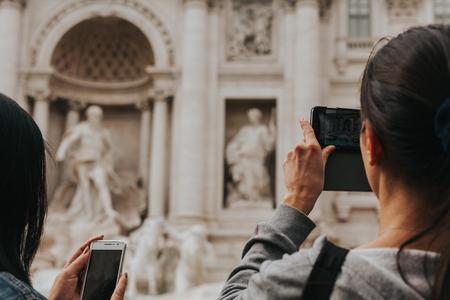 People taking photos in Fontana di Trevi, Rome.