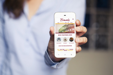 hand phone: Travel website template design in a mobile phone. Woman holding smart phone in the hand. Stock Photo