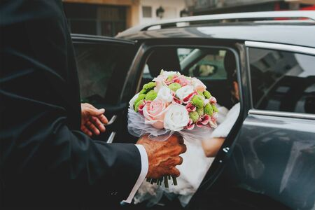 godfather: Detail of godfather holding a flower bouquet for the bride, that is getting off of the car.