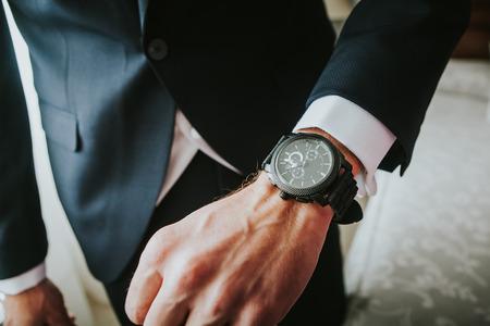 puntualidad: reloj de lujo nueva marca en una muñeca de hombre. Negocio. Foto de archivo