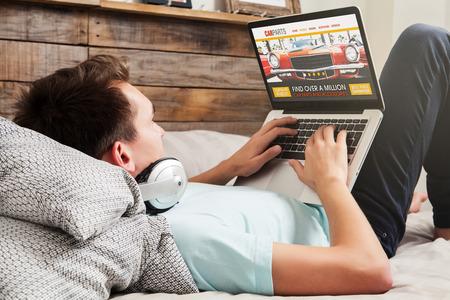 Auto-onderdelen zoeken. Auto reparatiewerkplaats website. Man op zoek naar auto-onderdelen op het internet.