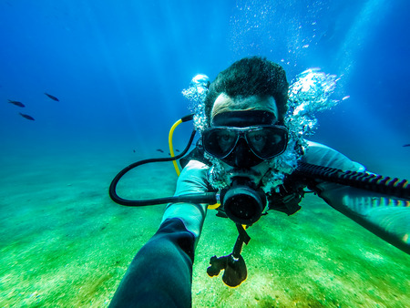 underwater diving: Man taking a photo of himself, while floating in the ocean floor for scuba diving. Stock Photo