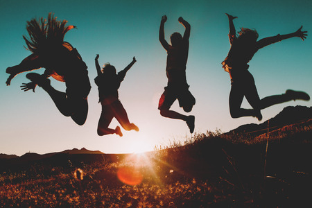 Three girls and a man jumping in the air, with the sun in the background.