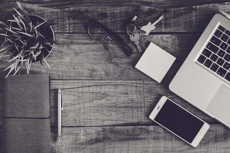 Top view of business and electronics stuff on a wooden desk. Black and white.