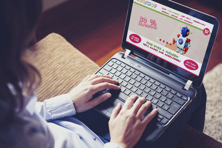 online world: Woman using internet to buy toys. Stock Photo