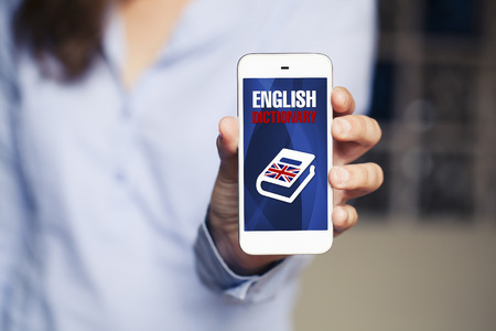 English dictionary: Learning english. Woman holding smart phone in the hand with english dictionary application in the screen.