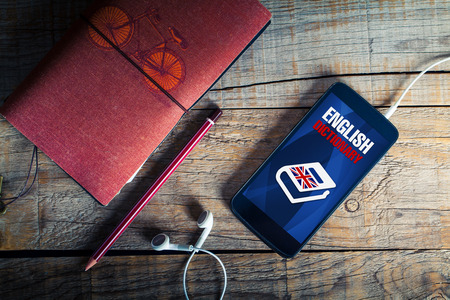 English dictionary: English dictionary. Top view of mobile, pencil, notebook and earphones, with english dictionary application on mobile screen. Stock Photo