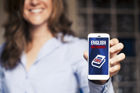 English dictionary: Learning english. Smiling woman holding smart phone with english dictionary application in the screen.