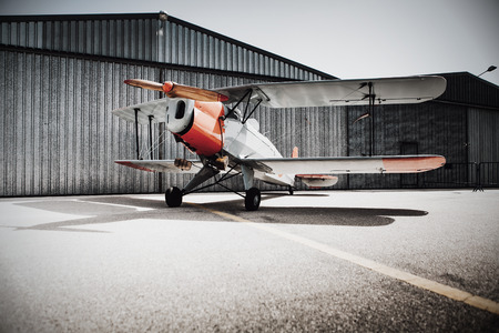 Vintage plane at the aerodrome, in front of the hangar. Stock Photo
