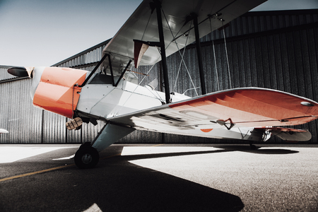 Vintage old plane in front of the hangar. Low angle side view. Stock Photo