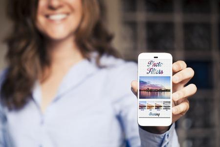 Glimlachende vrouw die een mobiele telefoon met foto filtert app op het scherm. Generieke app template design.