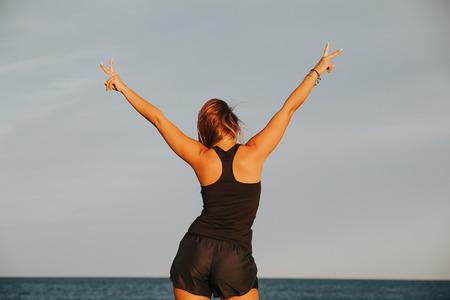 Mujer de la aptitud en sus espaldas haciendo el signo de victoria con dos manos.