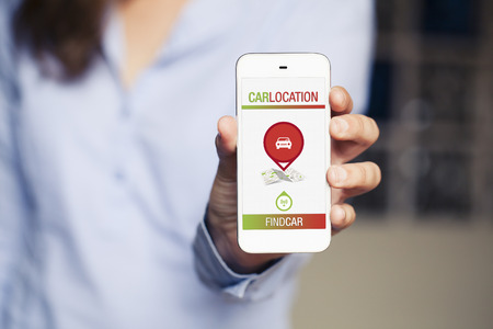 locating: Car locating software app in a mobile screen. Womans hand holding phone.