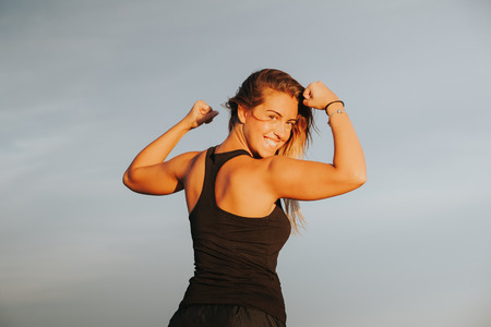 Fitness success concept. Woman showing muscle and looking at camera. Banco de Imagens